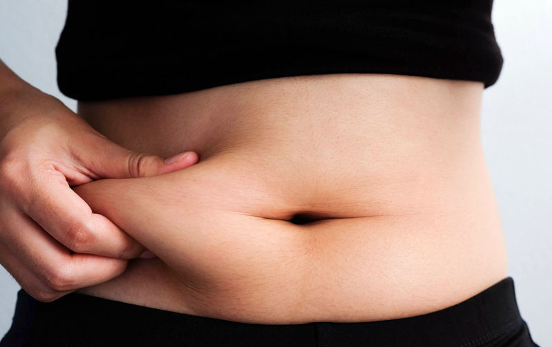 Midsection Of Woman Touching Stomach Against White Background