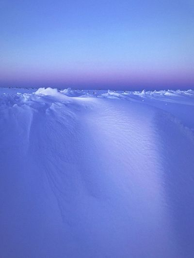 Scenic view of frozen sea against blue sky