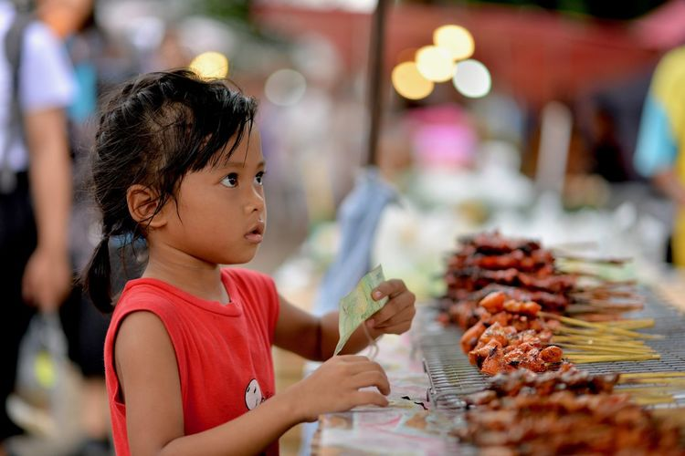 Girl buying barbecue at market stall