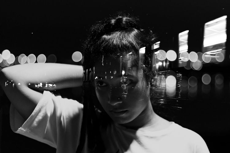 Double exposure image of woman and illuminated train at night
