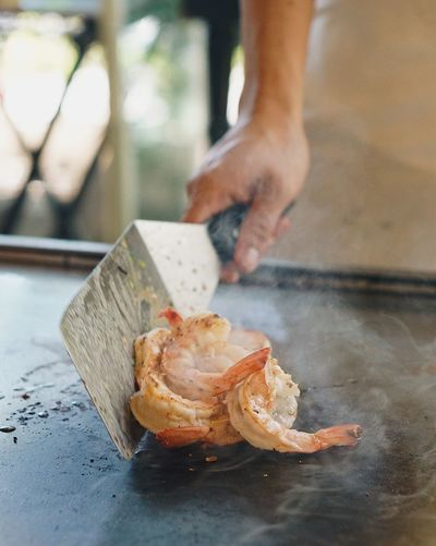 Close-up of man preparing prawns on frying pan