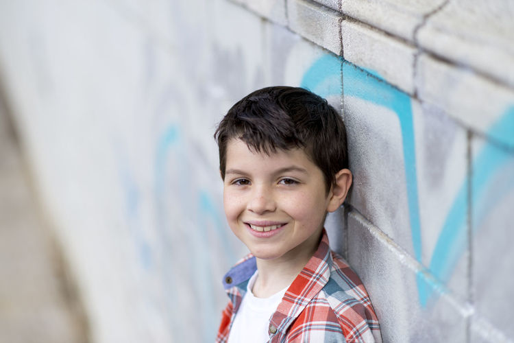 portrait of a casual teen boy, outdoors Portrait Child Wall - Building Feature One Person Looking At Camera Males  Childhood Smiling Happiness Boys Headshot Architecture Emotion Offspring Men Day Education Outdoors Innocence Pre-adolescent Child Adolescence