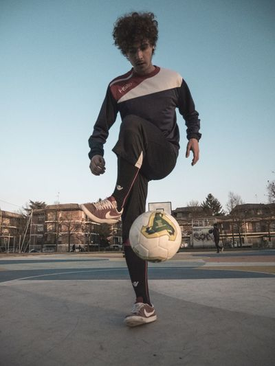 Soccer trick Full Length Young Adult Young Men One Person Leisure Activity Casual Clothing Afro Lifestyles City One Man Only Day Clear Sky Men One Young Man Only Outdoors Curly Hair Happiness Built Structure Real People Standing EyeEmNewHere EyeEm Ready