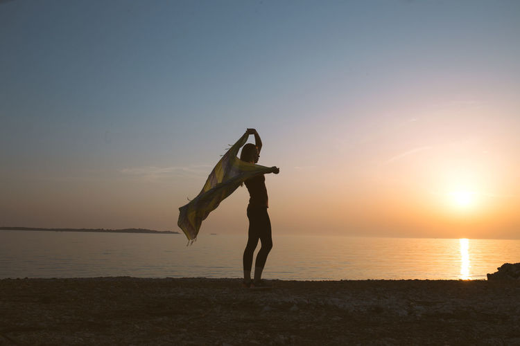 Full length of person on beach against sky during sunset