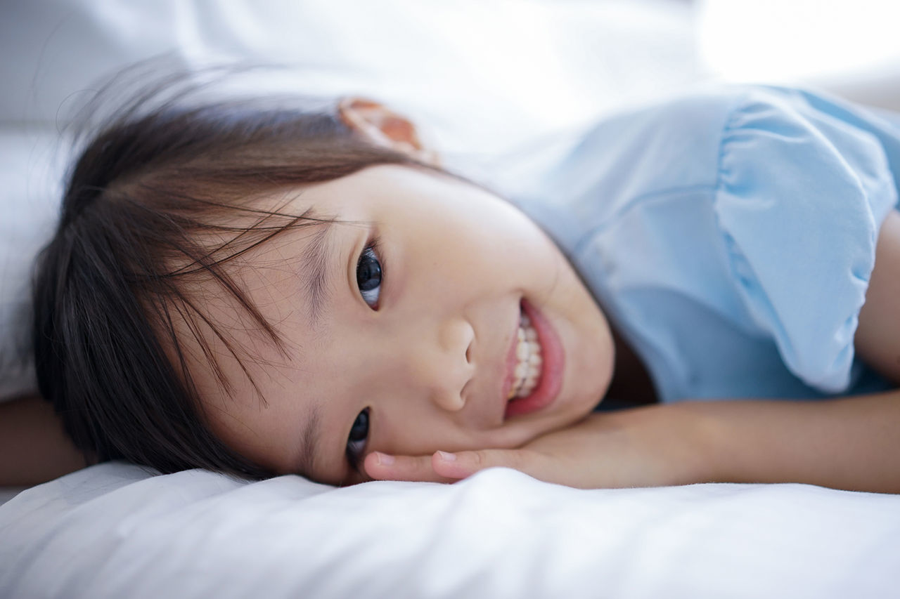 Close-up portrait of smiling girl lying on bed at home
