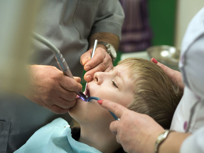 Midsection Of Dentist Examining Boy At Hospital