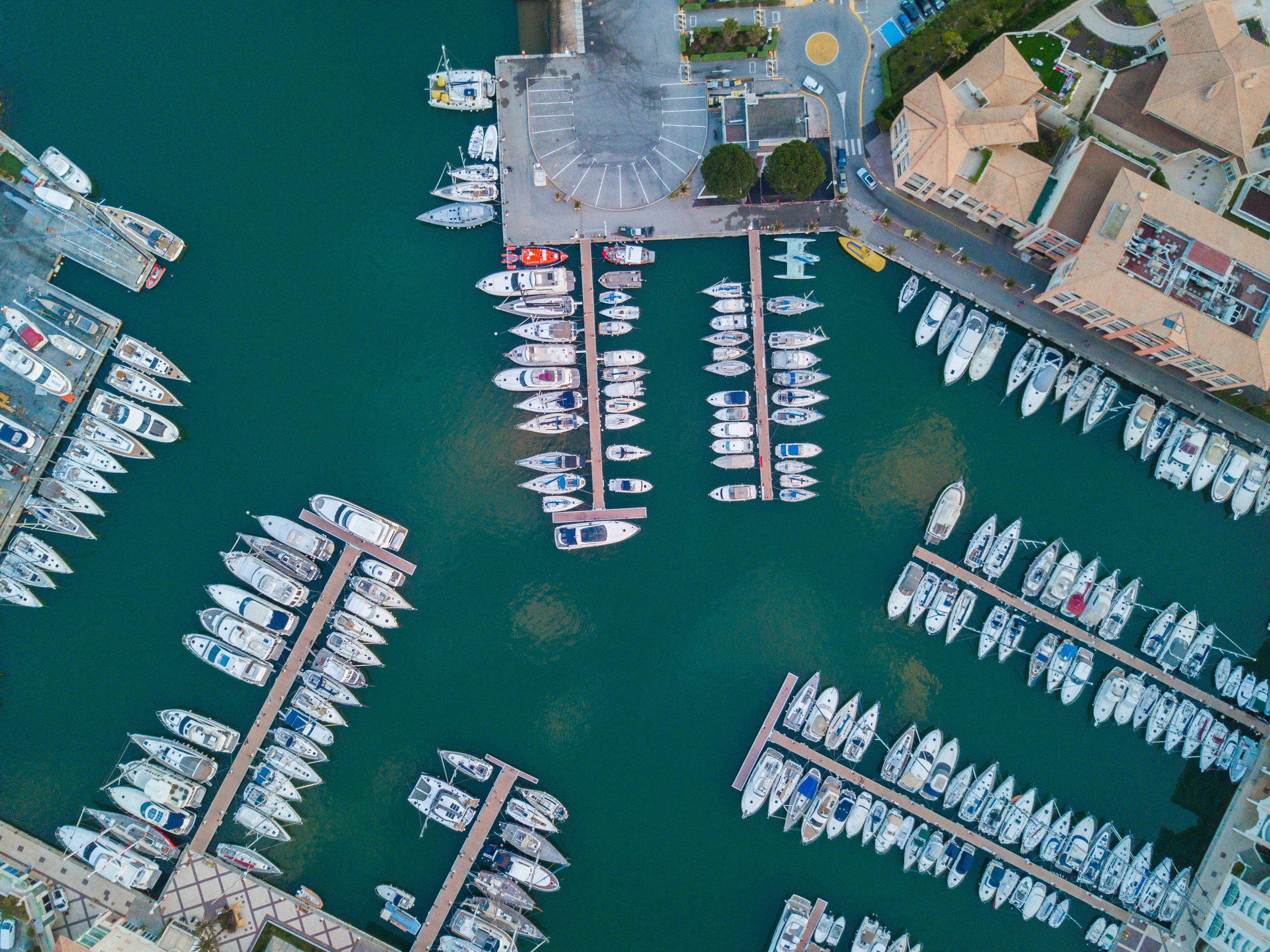 water, architecture, transportation, high angle view, building exterior, nautical vessel, no people, built structure, nature, waterfront, mode of transportation, day, outdoors, building, commercial dock, industry, sea, travel, shipping, turquoise colored