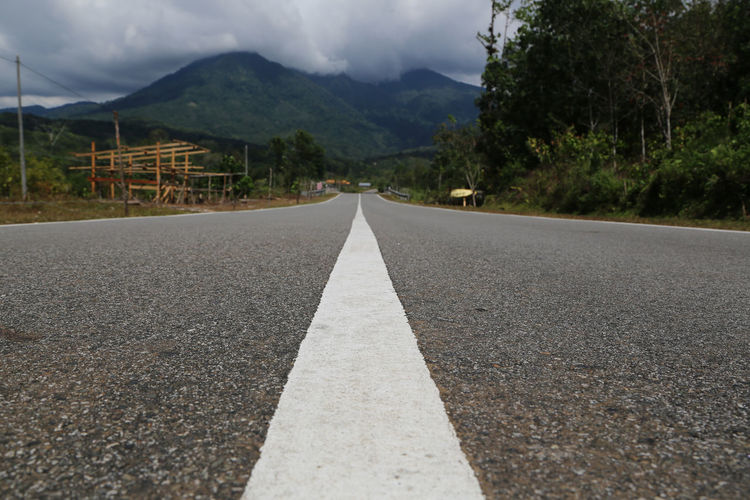 Sky Plant vanishing point Mountain Range Surface Level Outdoors No People Asphalt Diminishing Perspective Nature Road Marking Marking Transportation Direction Symbol Day Tree The Way Forward Mountain Road Sign Dividing Line Long