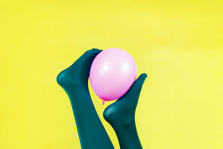 Studio Shot Yellow Multi Colored Colored Background Balloon Indoors  One Person Human Body Part Yellow Background Human Hand Body Part Copy Space Pink Color Close-up Celebration Vibrant Color Holding Green Color Green Background Purple Feet Tights Socks Leg