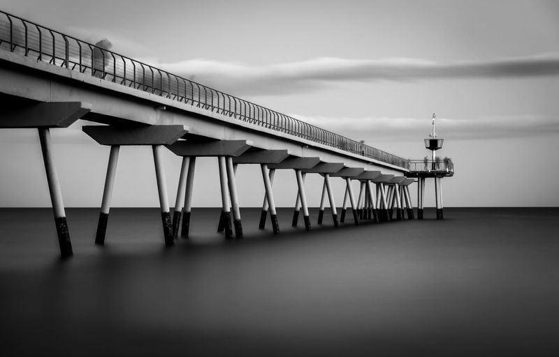 Sky Architecture Built Structure Cloud - Sky No People Day Water Nature Building Exterior Railing Outdoors Sea Building Pier Low Angle View Overcast Reflection Waterfront Pont Del Petroli Pont Del Petroli, Badalona, Spain Long Exposure Clouds Calm Place