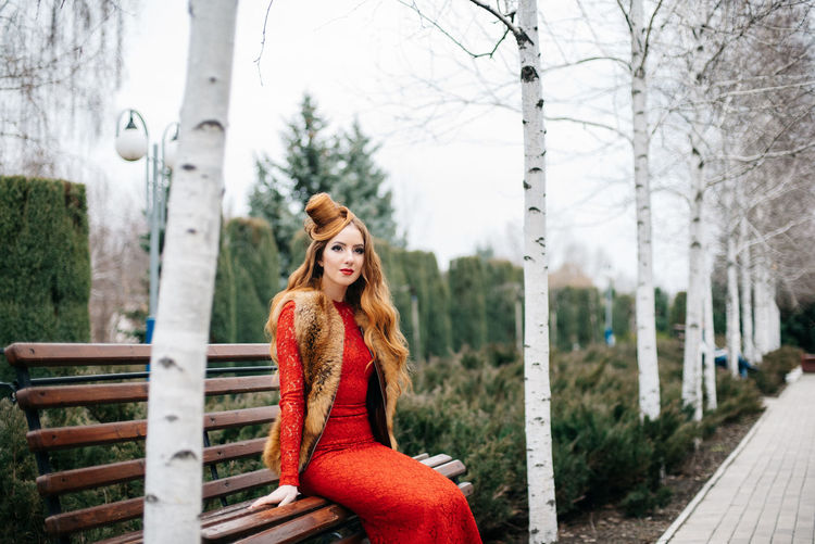 Portrait of woman sitting in park during winter