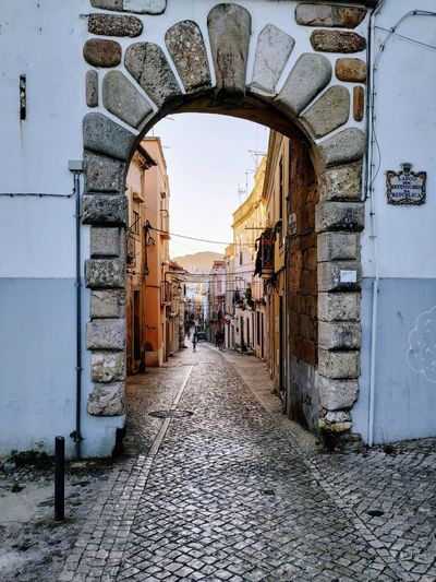 a new town Child City Arch Architecture Sky Built Structure Pedestrian Walkway Archway Gate Street Scene Cobblestone The Way Forward Entryway Passageway Footpath vanishing point Entrance City Gate Entry Passage Pavement Pedestrian Elevated Walkway
