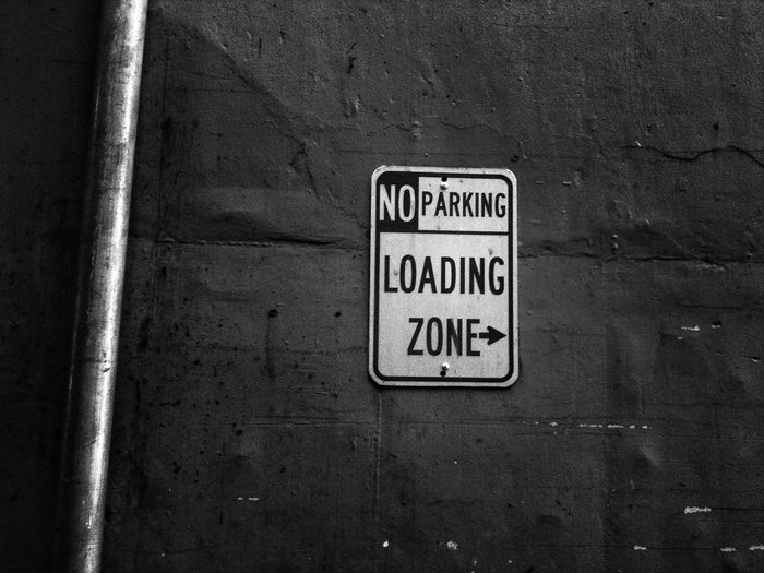 No Parking Sign And Loading Sing On Wall