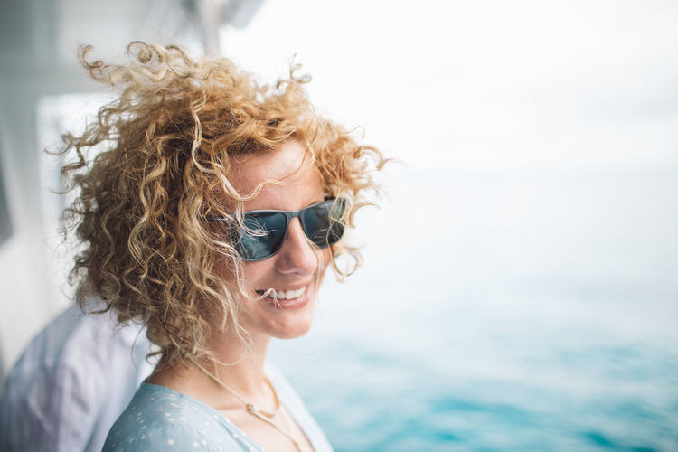 Smiling woman wearing sunglasses against sea