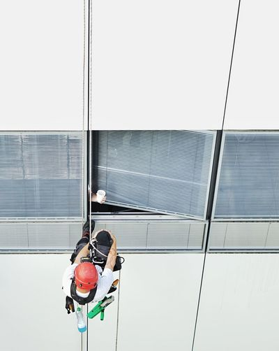 Low angle view of men on glass building