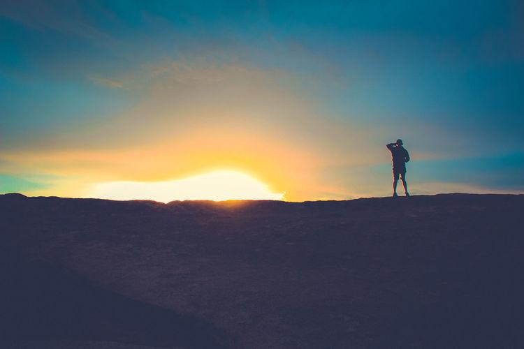 Silhouette Man Standing In Desert Against Sky During Sunset