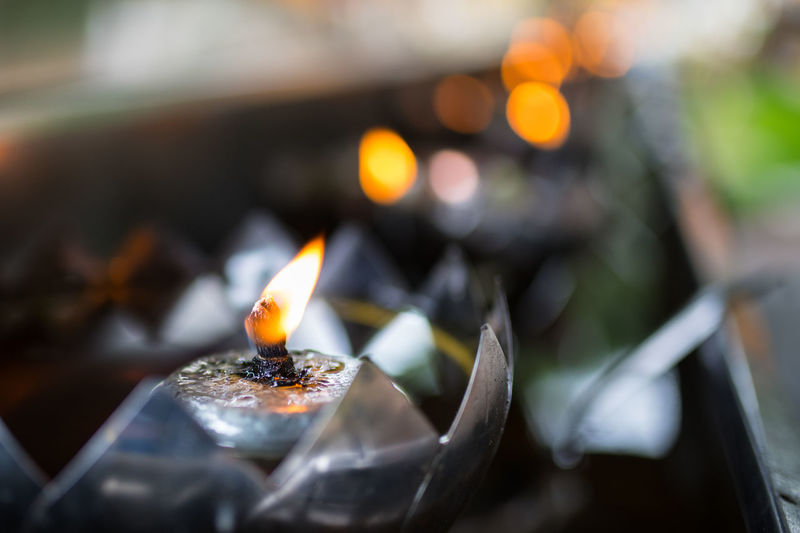 Close-up of burning candle in temple