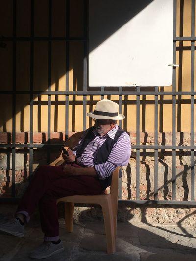 Senior man sitting on seat by wall