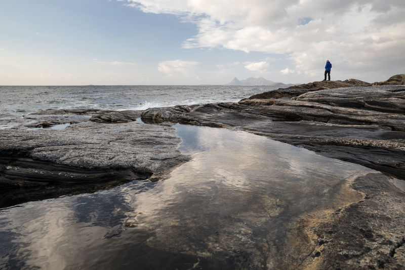 Man standing on huge rock by the sea looking to the horizon Looking Away Norwegian Sea Reflection Rock Formation Beauty In Nature Cloud - Sky Day Full Length Horizon Over Water Leisure Activity Men Nature One Person Outdoors People Puddle Real People Rear View Relaxation Rock - Object Sea Sky Standing Tranquil Scene Water Lost In The Landscape
