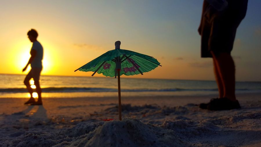 People by drink umbrella at beach against sky during sunset