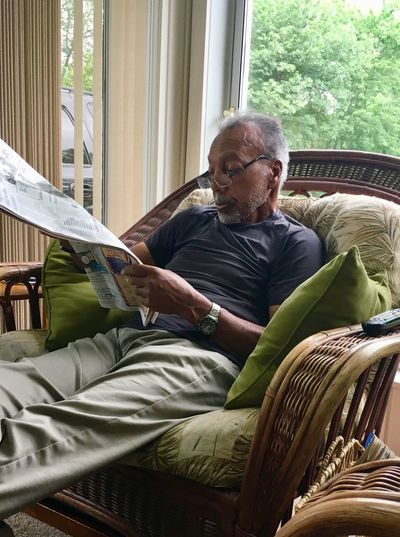 Man reading newspaper while sitting on seat at home
