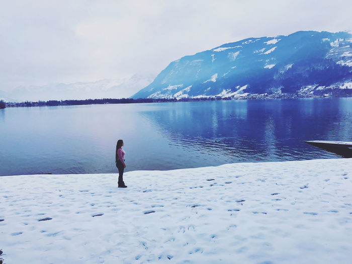 Woman standing on snowcapped land by lake against sky