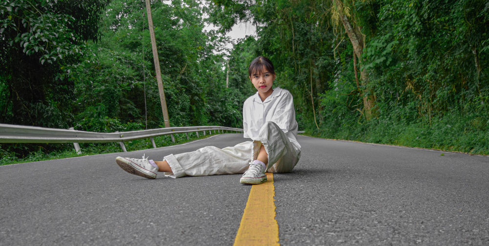 Portrait of a smiling young woman sitting on road