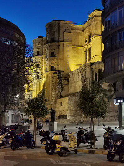 People riding motorcycle on road against buildings in city