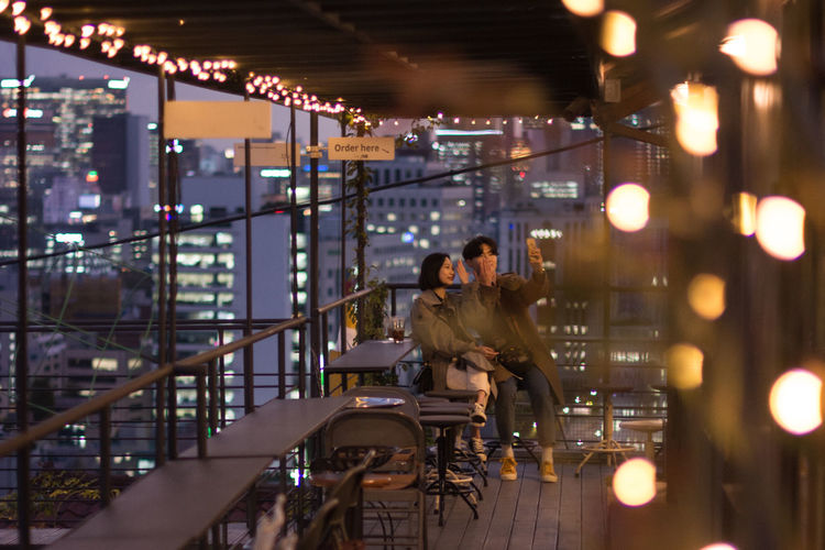 Evening calm Couple Illuminated Real People Sitting Ihwa-Dong City Terrace Terrace View Blue Hour Cityscape Blue Hour Selfie Time Traveling Travel Photography Triasia Trip Korea Bar With A View Human Connection A New Perspective On Life Holiday Moments Capture Tomorrow
