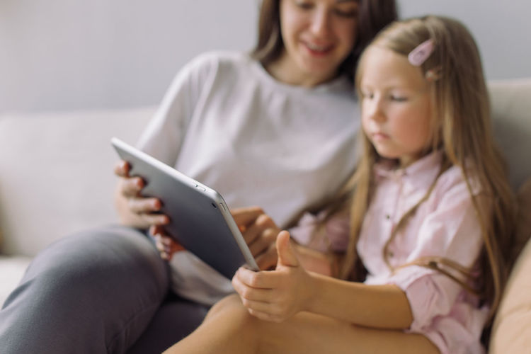 Close-up of woman using digital tablet with daughter