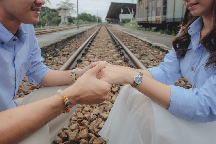 Midsection of couple holding hands on railroad track