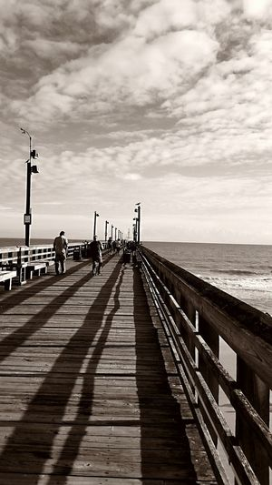Wooden Pier Fishing Pier On The Ocean People Walking  Going Fishing Light And Shadow Wooden Benches Clouds And Sky Black And White Photography Shades Of Grey