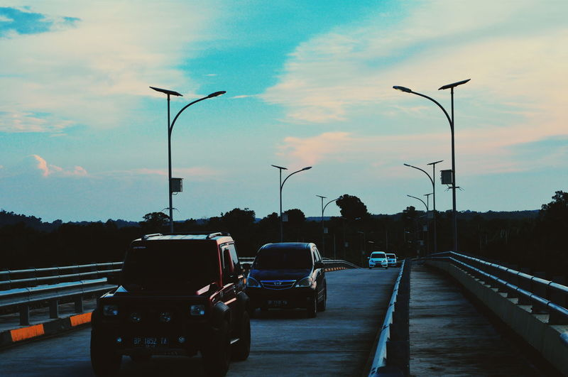 Vehicles on road against sky during sunset