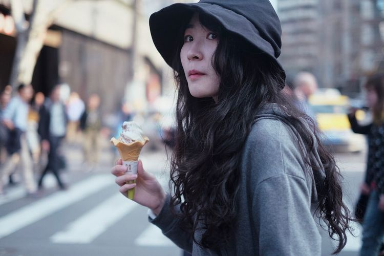 Side View Of Woman Holding Ice Cream While Standing On Street In City