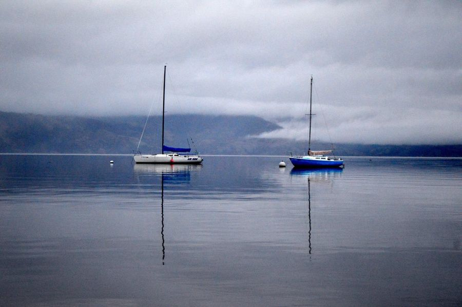 Still waters, vibrant reflections Lake Travel Boats Marine Boat Fog Mist Vibrant Color Reflection Mirror Reflection Water Sea Nautical Vessel Sky Nature Transportation Day Tranquility Tranquil Scene Sailboat Mast Sailing Horizon Over Water Beauty In Nature Outdoors No People Cloud - Sky Scenics