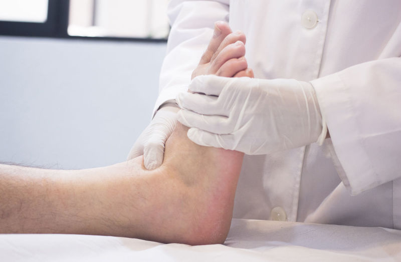 Midsection of doctor examining patient foot in hospital