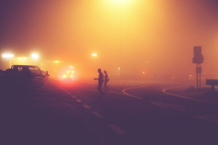 Silhouette People Crossing Road At Night During Foggy Weather