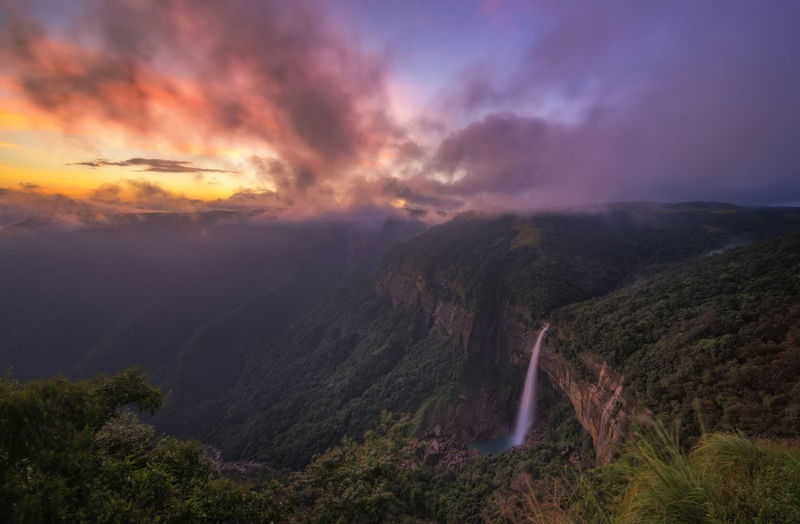 Scenic view of waterfall on mountain against sky during sunset