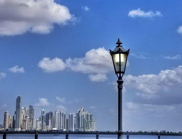 Street light by building against sky