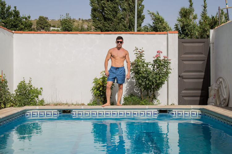 Full length of shirtless man in swimming pool against trees