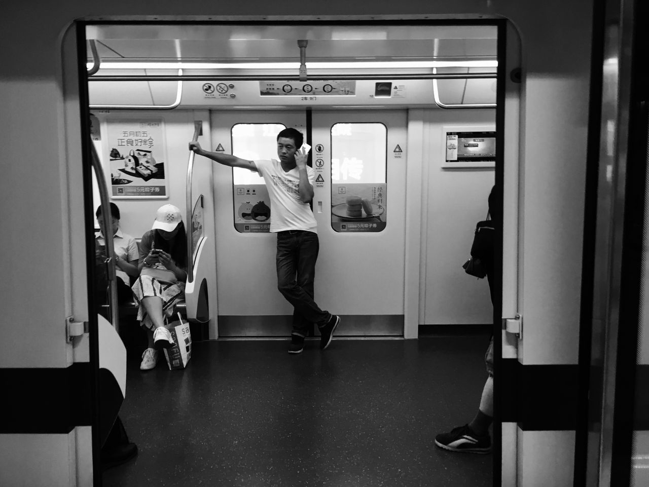 real people, full length, men, indoors, transportation, standing, train - vehicle, public transportation, one person, lifestyles, subway train, illuminated, laundromat, day, people