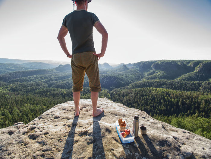 Resting mountaineer stay without shoes on view point. tourist brink metal flask and healthy meal.
