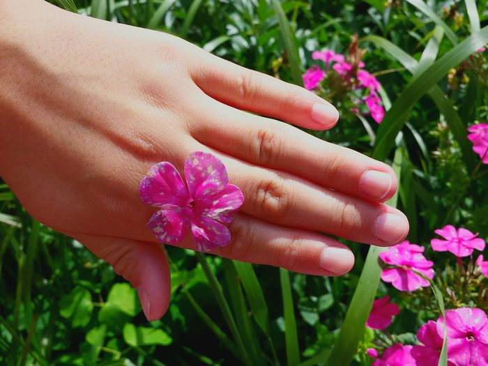 Cropped image of woman with pink flower in garden