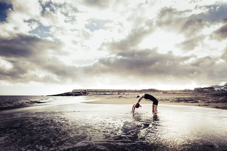 Side View Of Young Woman Practicing Yoga In Bridge Position At Beach Against Cloudy Sky
