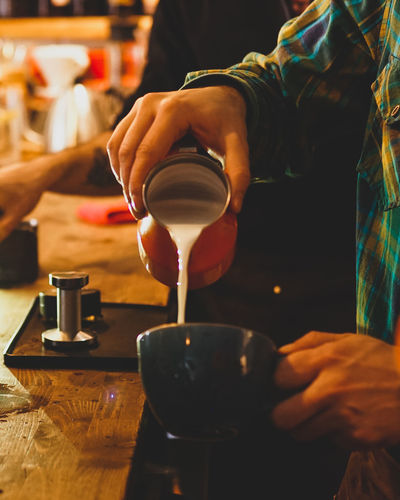 Midsection of barista preparing coffee in cafe