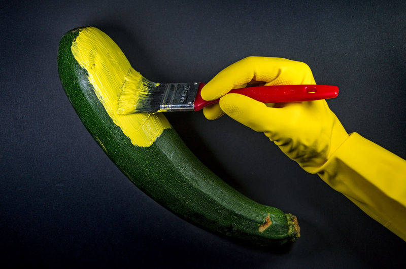 Cropped Hand Painting Zucchini Against Black Background