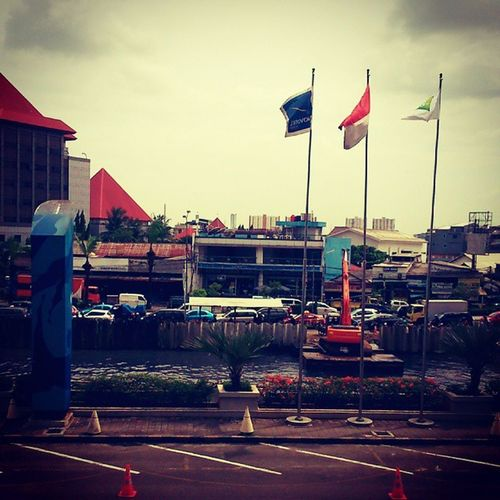 Three flags near to parking area. But, Can u see the escavator floating on the river outside the window?? Archimedes's law. Escavator Float Floating River outside window Archimedes jakarta jakartautara Indonesia three flags flag park parking area