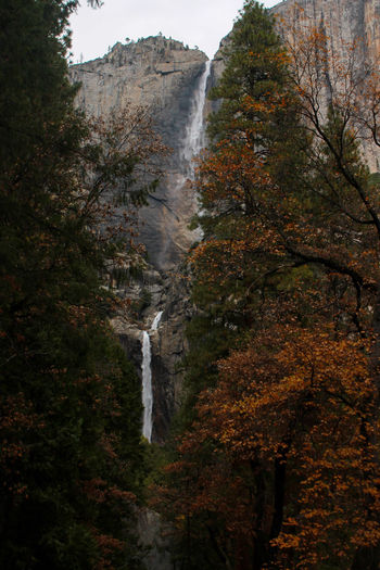 Scenic view of waterfall against sky during autumn