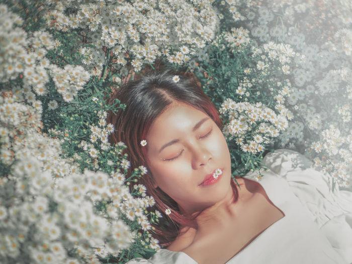 Portrait of beautiful woman by flower plants