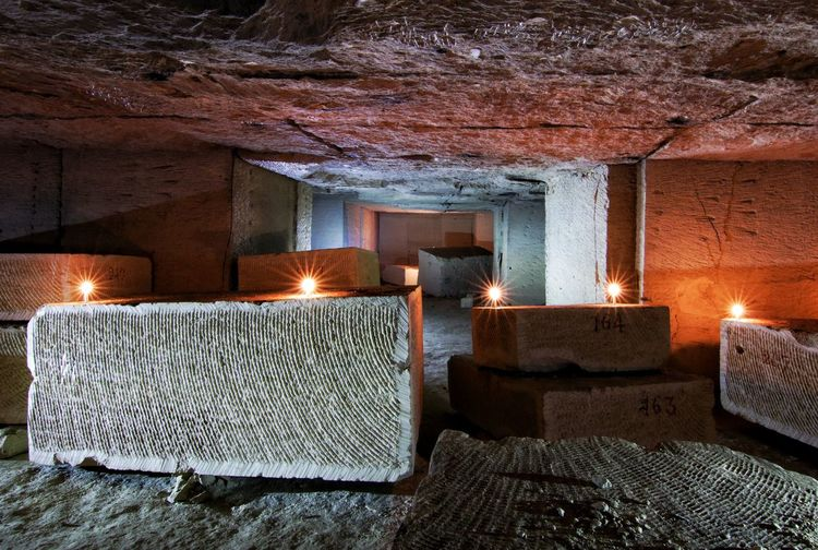 Illuminated candles on rock at archaeological site